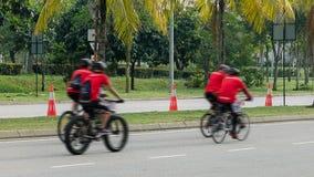 De groep fietsers berijdt langs stadsweg, vier mensen op fietsenrit onderaan straat stock foto's