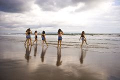 De groep gelukkige en opgewekte jonge vrouwen die hebbend pret op mooi zonsondergangstrand in de vakantie van de meisjeszomer haa royalty-vrije stock fotografie