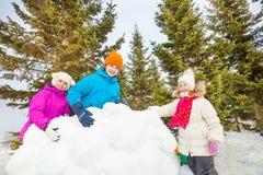 De groep gelukkige jonge geitjes bouwt achter sneeuwmuur Royalty-vrije Stock Foto