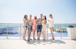 De groep gelukkige jongeren in gekleurde kleren drinkt champagne bij een luxehotel dichtbij het strand Heel wat jongelui stock afbeelding
