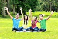 De groep gelukkige jongeren heft hun handen op Stock Afbeelding