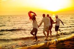 De groep gelukkige jongeren loopt op achtergrond van zonsondergangstrand en overzees Royalty-vrije Stock Foto's