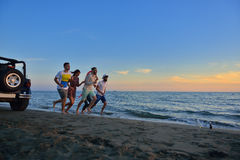 De groep gelukkige jongeren loopt op achtergrond van zonsondergangstrand en overzees Stock Foto's