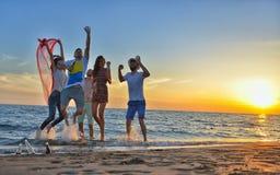 De groep gelukkige jongeren loopt op achtergrond van zonsondergangstrand en overzees Royalty-vrije Stock Foto