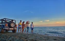 De groep gelukkige jongeren loopt op achtergrond van zonsondergangstrand en overzees Royalty-vrije Stock Fotografie
