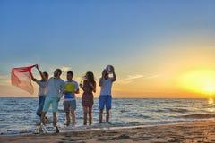 De groep gelukkige jongeren loopt op achtergrond van zonsondergangstrand en overzees Stock Foto