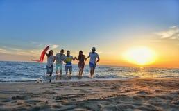 De groep gelukkige jongeren loopt op achtergrond van zonsondergangstrand en overzees Stock Fotografie