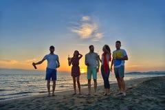 De groep gelukkige jongeren loopt op achtergrond van zonsondergangstrand en overzees Stock Afbeelding