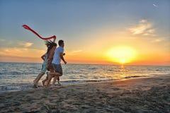 De groep gelukkige jongeren loopt op achtergrond van zonsondergangstrand en overzees Royalty-vrije Stock Afbeeldingen