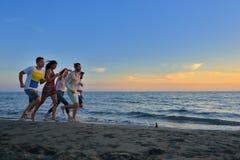 De groep gelukkige jongeren loopt op achtergrond van zonsondergangstrand en overzees Stock Afbeeldingen