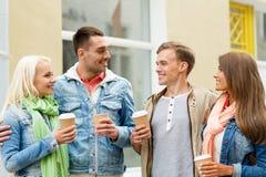 De groep glimlachende vrienden met haalt koffie weg royalty-vrije stock afbeeldingen