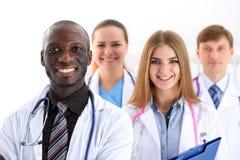 De groep glimlachende vriendschappelijke geneeskunde artsen kijkt in camera stock foto's