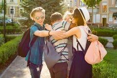 De groep de jeugd heeft pret, het gelukkige tienersvrienden lopen, die genietend van dag in de stad spreken royalty-vrije stock afbeeldingen