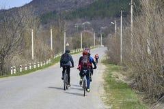 De groep jonge fietsers drijft langs een asfaltweg royalty-vrije stock afbeeldingen