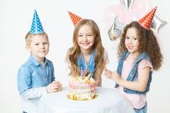De groep jonge geitjes in feestelijk GLB zit dichtbij verjaardagscake en glimlach viering De partij van de verjaardag Ballons op  Royalty-vrije Stock Afbeelding