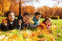 De groep jonge geitjes lag in de herfstbladeren Royalty-vrije Stock Afbeelding