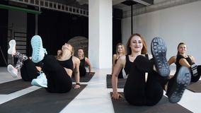 De groep jonge gelukkige atleten voert geschiktheidsaerobics op de vloer in geschiktheidsklasse uit Concept yoga, fitness, sport stock footage
