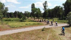De groep jonge mannelijke fietsers achtervolgt leider bij het ras van de bergfiets in Muromets-Park stock videobeelden