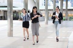 de groep jonge onderneemster bij spitsuur die in de straat lopen en let op de klok controlerend tijd aan laat op stadsstraten royalty-vrije stock foto
