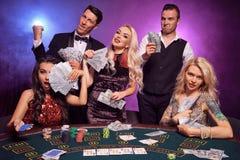 De groep jonge rijke vrienden speelt pook bij een casino stock afbeeldingen