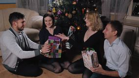 De groep Jongeren geeft voorstelt aan elkaar onder de Boom in het Kerstmisbinnenland, Nieuwjaarviering stock videobeelden