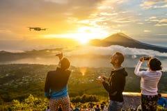 De groep jongeren let op de dageraad bovenop Batur Stock Foto's