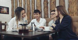 De groep jongeren van twee paren van kerels en de meisjes hebben een theetijd in de koffie en absorbedly het kijken op smartphone Royalty-vrije Stock Fotografie