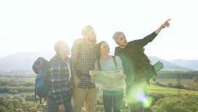 De groep Kaukasische reizigersvrienden controleert de kaart die de juiste manier op bergbovenkant bij zonsondergang proberen te w stock footage