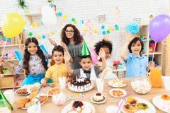 De groep kinderen met kleurenballons zit achter feestelijke lijst waarop de tribunes koeken Royalty-vrije Stock Afbeeldingen
