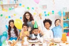 De groep kinderen met kleurenballons zit achter feestelijke lijst waarop de tribunes koeken Stock Afbeelding
