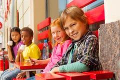 De groep kinderendiversiteit zit buiten in koffie Stock Foto's