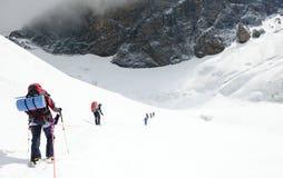 De groep klimmers bereikt de bovenkant van bergpiek Het beklimmen en Royalty-vrije Stock Afbeelding