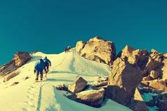 De groep klimmers bereikt de bovenkant van bergpiek Het beklimmen en royalty-vrije stock fotografie