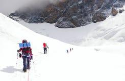 De groep klimmers bereikt de bovenkant van bergpiek Het beklimmen en Stock Foto's
