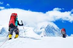 De groep klimmers met rugzakken bereikt de top van bergpiek Succes, vrijheid en geluk, voltooiing in bergen royalty-vrije stock fotografie