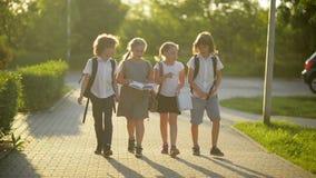 De groep Leerlingen met Schoolrugzakken keert naar School terug Zij hebben heel wat Pret stock videobeelden