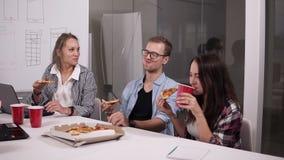 De groep mannelijke en vrouwelijke medewerkers die middagpauze hebben die pizza samen in bureau eten, jongelui kleedde terloops p stock footage