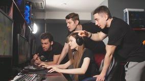 De groep mannelijke gamers verzamelt zich rond de vrouwelijke speler, die hard over spelstrategie denkt stock footage