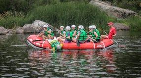 De groep mannen en vrouwen, geniet water van rafting activiteit bij rivier Rafting op Pivdennyi Buh stock afbeeldingen