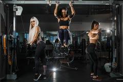 De groep meisjes leidt met TRX-riemen en hogere toi van de blok parallelle greep de borst in de gymnastiek op Zij dragen stock foto