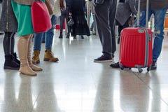 De groep mensen bevindt zich met koffers en zakken die zich in de luchthavenzaal bevinden stock foto