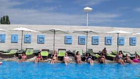 De groep mensen doet aerobics in openlucht voor benen op terrasa naast blauwe poolside stock footage