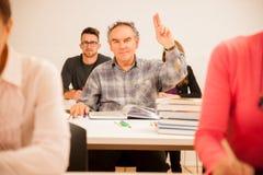 De groep mensen van verschillende leeftijdszitting in klaslokaal en is aanwezig Royalty-vrije Stock Fotografie