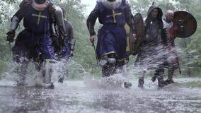De groep middeleeuwse militairen loopt op de vulklei in langzame motie stock videobeelden