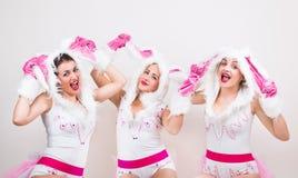 De groep mooie meisjes in konijnkostuum voelt opgewekt omhoog opheffend hun oren Royalty-vrije Stock Foto's