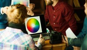 De groep ontwerpers bespreekt het kleurenpalet in een modern bureau Stock Foto