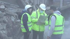 De groep reddingsarbeiders onderzoekt de kaart na een aardbeving of een orkaan stock footage