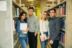 De groep student wil wat nuttige literatuur aan het voorbereidingen treffen voor universitair examen vinden Twee jongens en twee  stock afbeelding