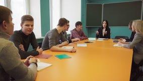 De groep studenten en een leraar zitten bij een lijst en een bespreking stock video