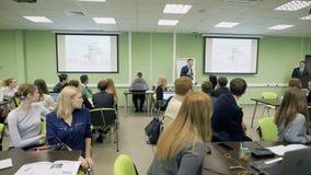 De groep studenten in klaslokaal bij de universiteit is aandachtig luisterend de lezing op Economie van beroemde Professor stock videobeelden